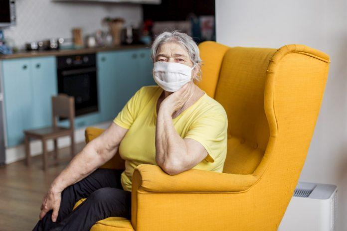 Adultos mayores con máscara protectora aún en interiores